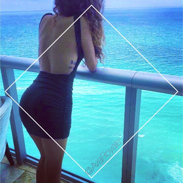 woman looking at blue sea in Backless Black halter neck dress